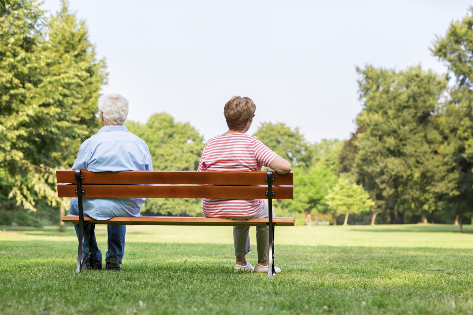 Senior couple on bench separated
